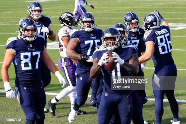 Wide receiver A.J. Brown of the Tennessee Titans celebrates with his team following a 10-yard touchdown reception during the first quarter of their...