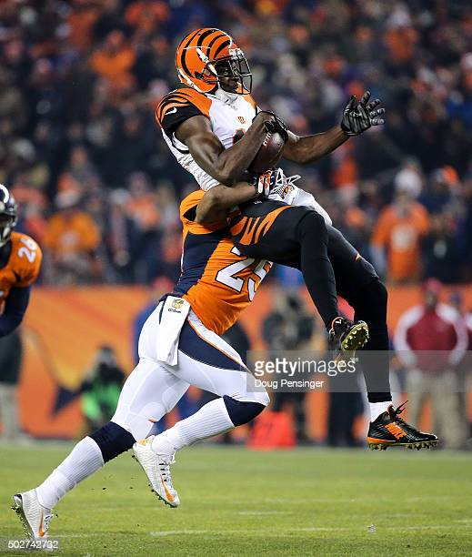 Wide receiver AJ Green of the Cincinnati Bengals is hit by cornerback Chris Harris of the Denver Broncos after a first quarter reception at Sports...
