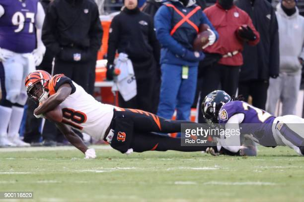Wide Receiver AJ Green of the Cincinnati Bengals is tackled after a reception by cornerback Brandon Carr of the Baltimore Ravens in the first quarter...