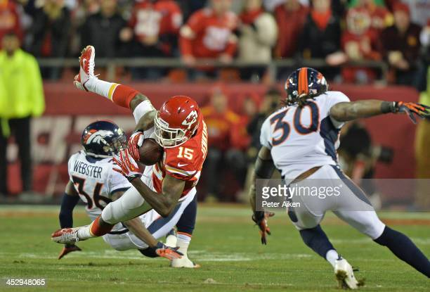 Wide receiver AJ Jenkins of the Kansas City Chiefs makes a catch between defenders Kayvon Webster and David Bruton of the Denver Broncos during the...