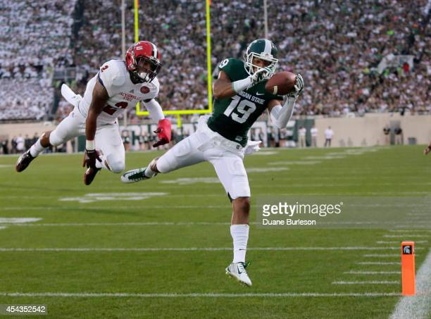 Wide receiver AJ Troup of the Michigan State Spartans catches a 17-yard touchdown pass against cornerback Jermaine Hough of the Jacksonville...
