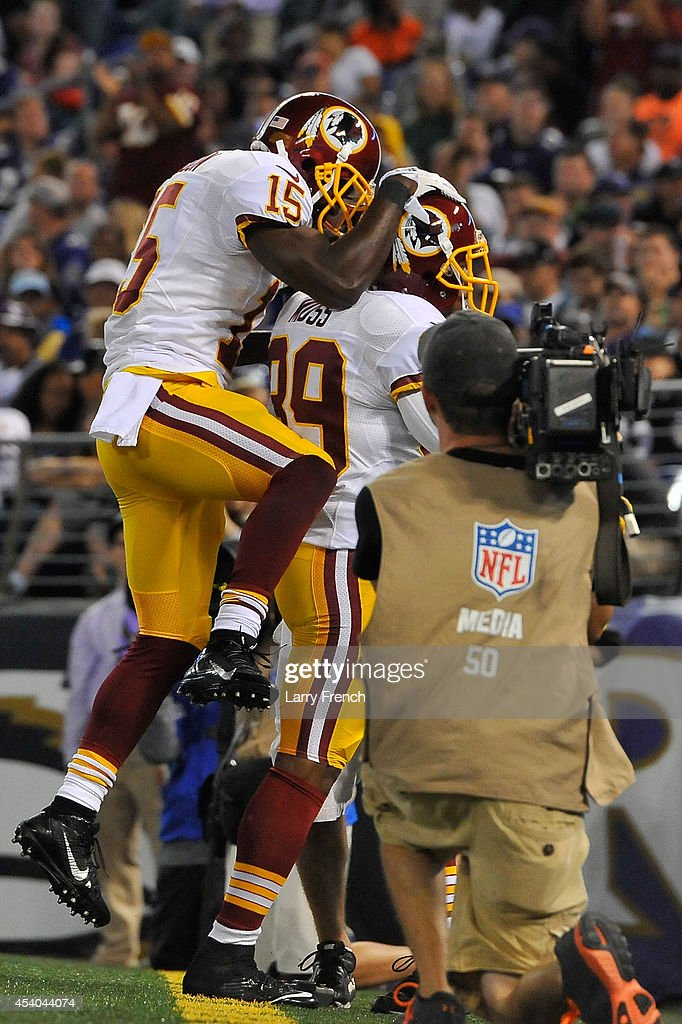 Wide receiver Aldrick Robinson #15 of the Washington Redskins celebrates with wide receiver Santana Moss #89 after Moss's touchdown catch during a preseason game against the Baltimore Ravens at M&T Bank Stadium on August 23, 2014 in Baltimore, Maryland.