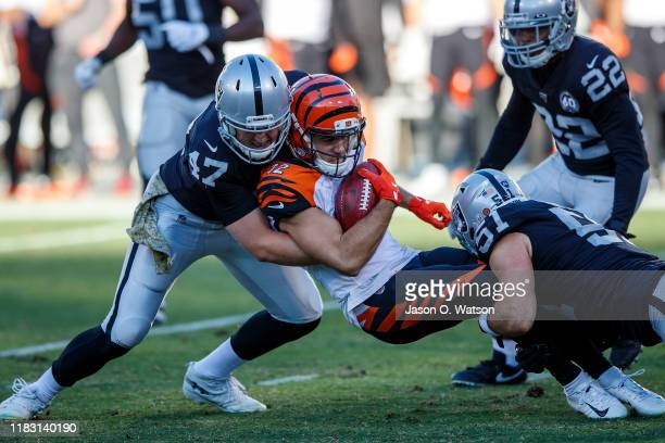 Wide receiver Alex Erickson of the Cincinnati Bengals is tackled by long snapper Trent Sieg of the Oakland Raiders and inside linebacker Will Compton...