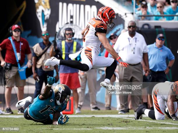 Wide Receiver Alex Erickson of the Cincinnati Bengals leaps over Wide Receiver Arrelious Benn of the Jacksonville Jaguars on a kickoff return during...