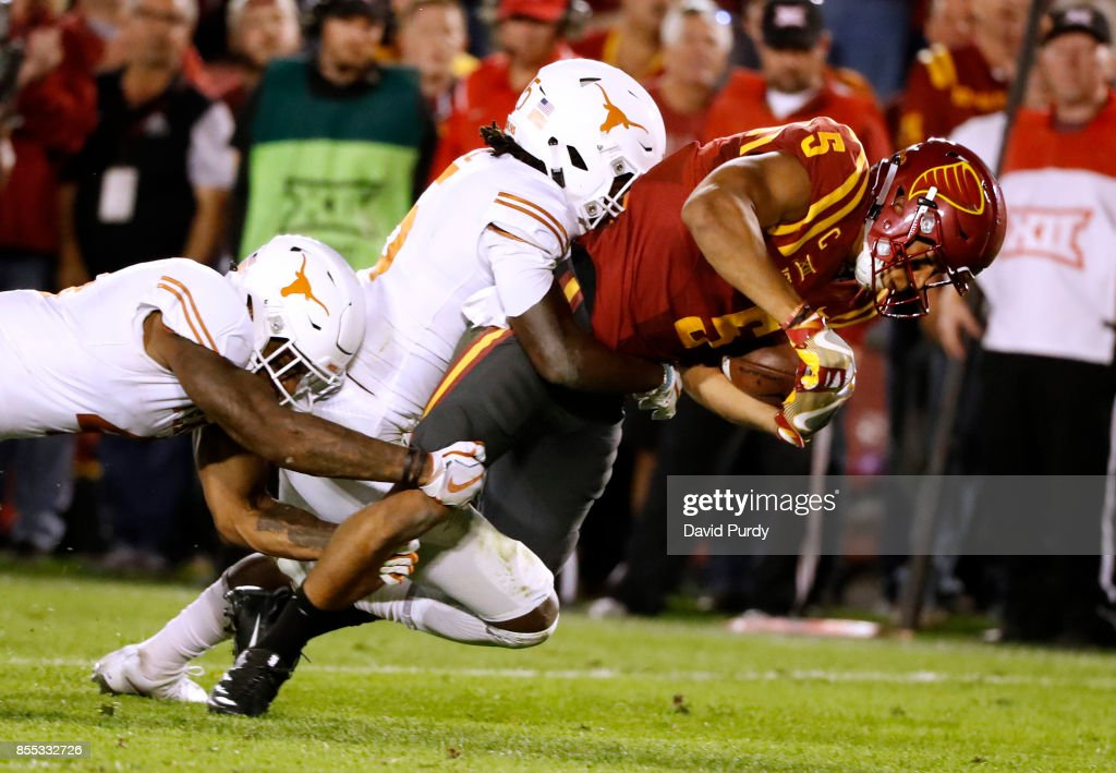 Wide receiver Allen Lazard #5 of the Iowa State Cyclones is tackled by defensive back DeShon Elliott #4, and defensive back Holton Hill #5 of the Texas Longhorns, as he rushed for yards in the second half of play at Jack Trice Stadium on September 28, 2017 in Ames, Iowa. The Texas Longhorns won 17-7 over the Iowa State Cyclones.
