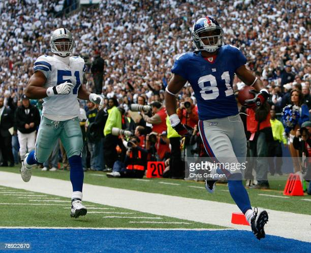 Wide receiver Amani Toomer of the New York Giants scores a 52 yard touchdown reception past Akin Ayodele of the Dallas Cowboys during the first...