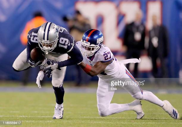Wide receiver Amari Cooper of the Dallas Cowboys carries against the defense of cornerback Deandre Baker of the New York Giants during the game at...