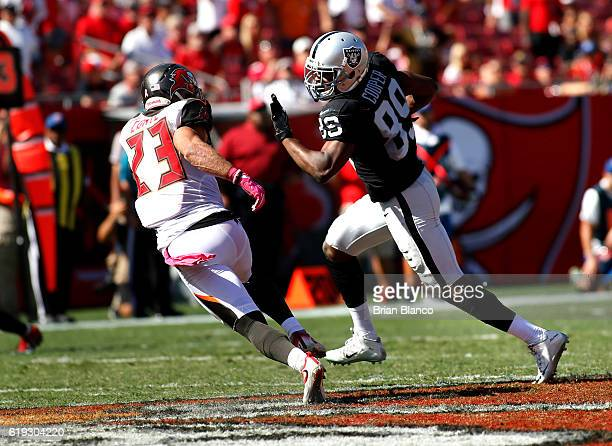 Wide receiver Amari Cooper of the Oakland Raiders evades strong safety Chris Conte of the Tampa Bay Buccaneers during a carry in the third quarter of...