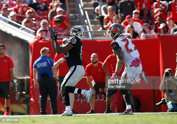 Wide receiver Amari Cooper of the Oakland Raiders hauls in a 34 yard pass from quarterback Derek Carr for a touchdown in front of strong safety Chris...