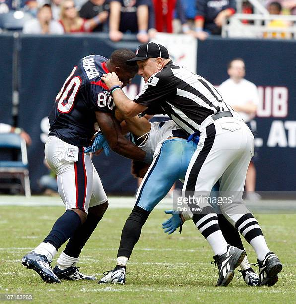 Wide receiver Andre Johnson of the Houston Texans is separated by umpire Garth DeFerlice from cornerback Cortland Finnegan of the Tennessee Titans...
