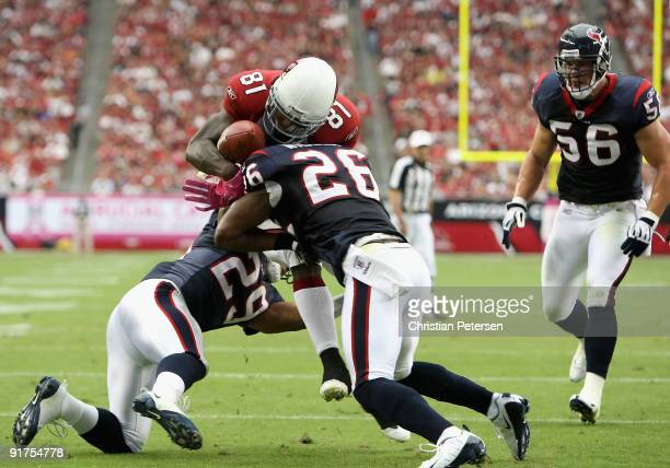 Wide receiver Anquan Boldin of the Arizona Cardinals has the ball knocked free after a reception by Eugene Wilson of the Houston Texans during the...