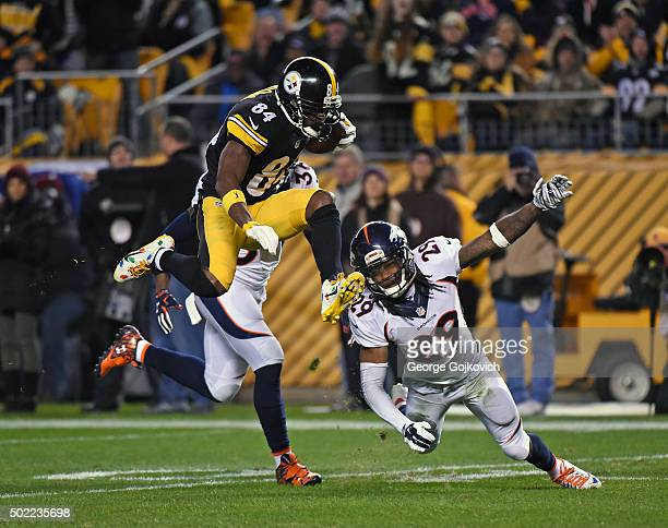 Wide receiver Antonio Brown of the Pittsburgh Steelers leaps as he tries to avoid cornerbacks Kayvon Webster and Bradley Roby of the Denver Broncos...