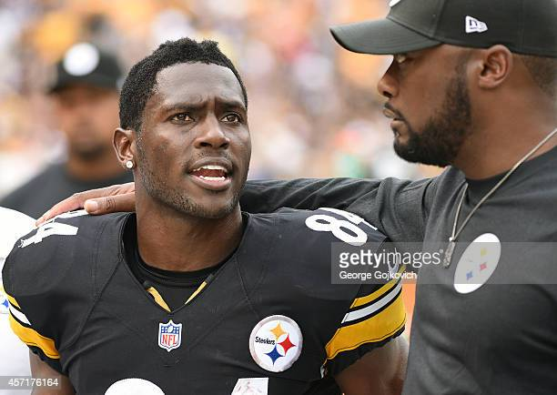 Wide receiver Antonio Brown of the Pittsburgh Steelers talks to head coach Mike Tomlin as they leave the field after the first half of a game against...