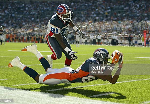 Wide receiver Ashley Lelie of the Denver Broncos stretches out but fails to hold on to a pass against cornerback Chris Watson of the Buffalo Bills in...