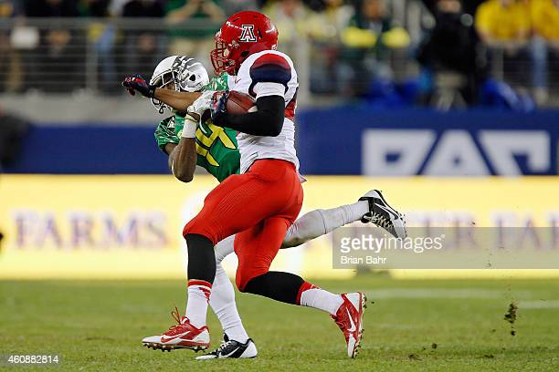 Wide receiver Austin Hill of the Arizona Wildcats picks up nine yards before the tackle by defensive back Ifo EkpreOlomu of the Oregon Ducks in the...