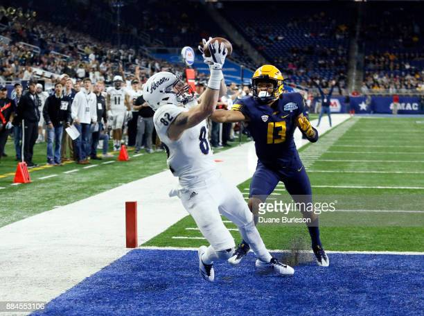 Wide receiver Austin Wolf of the Akron Zips catches a touchdown pass against defensive back Ka'dar Hollman of the Toledo Rockets during the second...