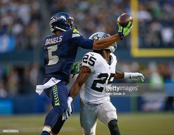 Wide receiver B.J. Daniels of the Seattle Seahawks battles cornerback D.J. Hayden of the Oakland Raiders at CenturyLink Field on September 3, 2015 in...