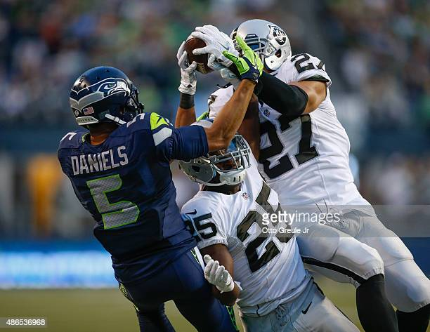 Wide receiver B.J. Daniels of the Seattle Seahawks battles cornerback D.J. Hayden and safety Taylor Mays of the Oakland Raiders at CenturyLink Field...