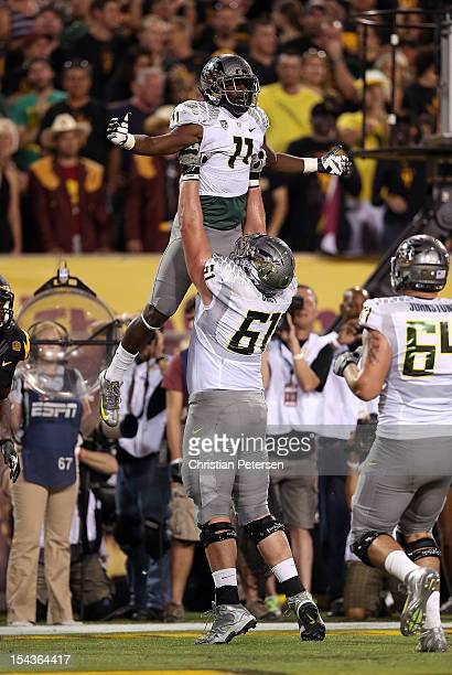 Wide receiver Bralon Addison of the Oregon Ducks is hoisted up in the air by offensive linesman Nick Cody after Addison scored a 6 yard touchdown...