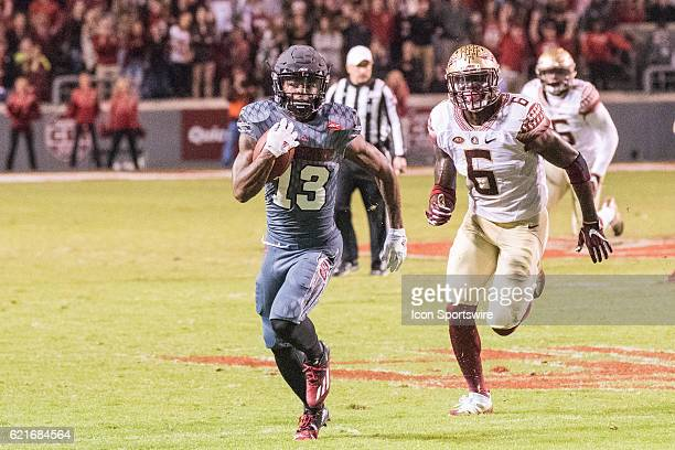 Wide receiver Bra'Lon Cherry of the North Carolina State Wolfpack races down the field as linebacker Matthew Thomas of the Florida State Seminoles...