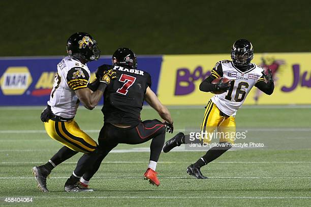 Wide receiver Brandon Banks of the Hamilton TigerCats carries the ball as team mate defensive back Delvin Breaux of the Hamilton TigerCats blocks...