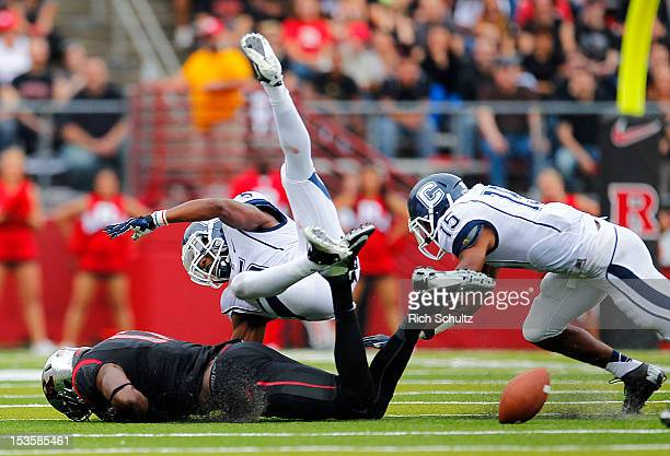 Wide receiver Brandon Coleman of the Rutgers Scarlet Knights has the ball knocked away by Blidi Wreh-Wilson and Ty-Meer Brown of the Connecticut...