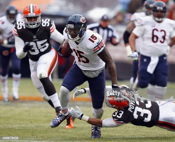 Wide receiver Brandon Marshall of the Chicago Bears runs the ball by defensive lineman Armonty Bryant and Jordan Poyer of the Cleveland Browns at...