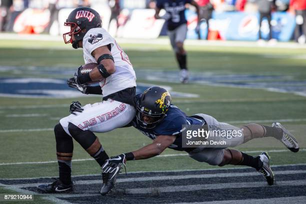 Wide receiver Brandon Presley of the UNLV Rebels is taken down by defensive back Daniel Brown of the Nevada Wolf Pack at Mackay Stadium on November...