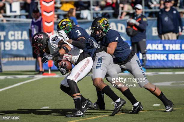 Wide receiver Brandon Presley of the UNLV Rebels tries to get away from defensive back Ahki Muhammad of the Nevada Wolf Pack at Mackay Stadium on...