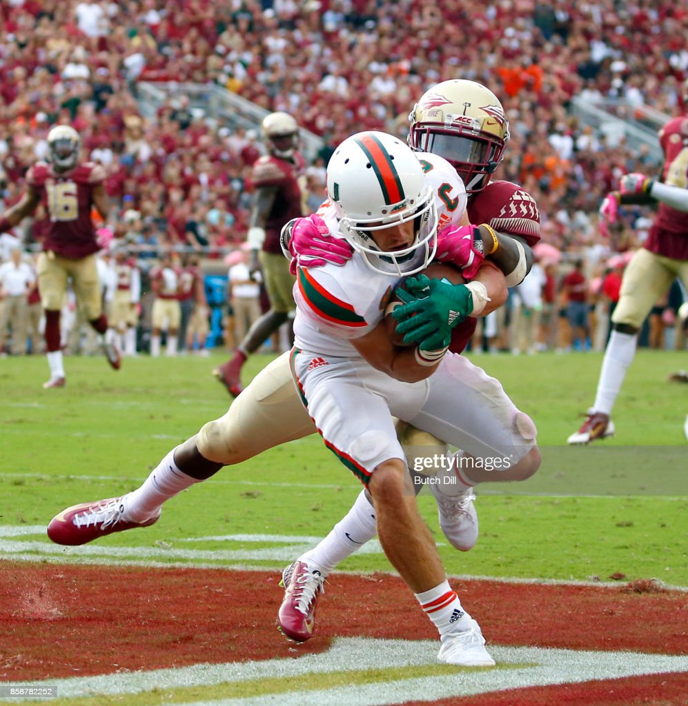 Wide receiver Braxton Berrios #8 of the Miami Hurricanes catches a pass over defensive back A.J. Westbrook #19 of the Florida State Seminoles for a touchdown during the second half of an NCAA football game at Doak S. Campbell Stadium on October 7, 2017 in Tallahassee, Florida.
