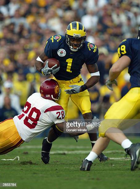 Wide receiver Braylon Edwards of the Michigan Wolverines attempts to break out of the grasp of cornerback Will Poole of the USC Trojans during the...