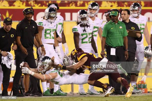 Wide receiver Brenden Schooler of the Oregon Ducks dives with the football ahead of defensive back Chase Lucas of the Arizona State Sun Devils during...