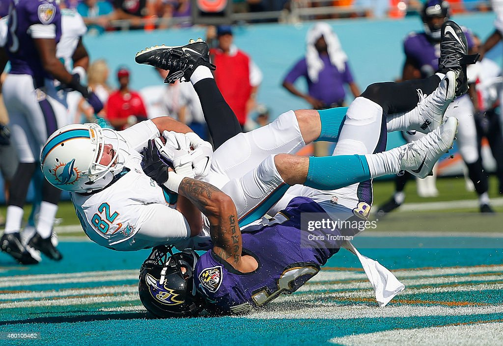 Wide receiver Brian Hartline #82 of the Miami Dolphins catches a first quarter touchdown pass as cornerback Asa Jackson #25 of the Baltimore Ravens defends during a game at Sun Life Stadium on December 7, 2014 in Miami Gardens, Florida.