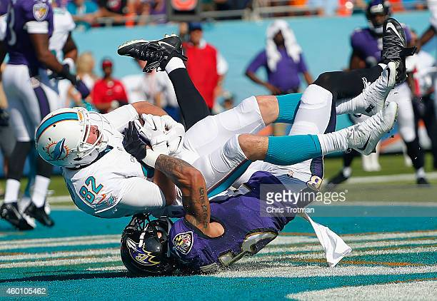 Wide receiver Brian Hartline of the Miami Dolphins catches a first quarter touchdown pass as cornerback Asa Jackson of the Baltimore Ravens defends...