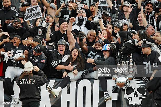 Wide receiver Brice Butler and linebacker Sio Moore of the Oakland Raiders jump into arms of fans in the Black Hole after defeating the San Francisco...