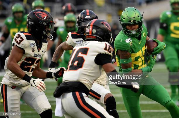 Wide receiver Bryan Addison of the Oregon Ducks runs with a pass reception as defensive back Isaiah Dunn and defensive back Akili Arnold of the...