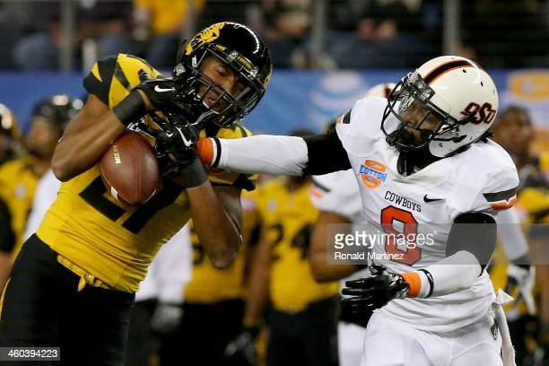 Wide receiver Bud Sasser of the Missouri Tigers is unable to make a catch as it's broken up by Daytawion Lowe of the Oklahoma State Cowboys in the...