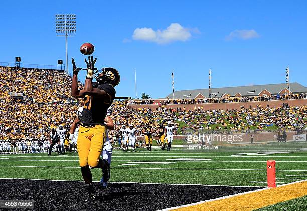Wide receiver Bud Sasser of the Missouri Tigers makes a catch in the end zone for a touchdown as defensive back Jordan Ozerities of the UCF Knights...