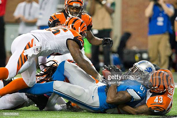 Wide receiver Calvin Johnson of the Detroit Lions catches a touchdown pass as he's tackled by strong safety George Iloka of the Cincinnati Bengals...