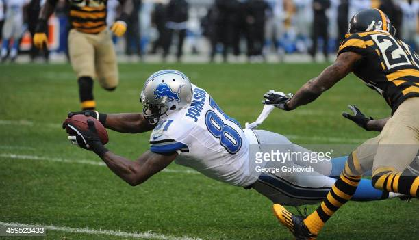 Wide receiver Calvin Johnson of the Detroit Lions falls forward after catching a pass against cornerback Ike Taylor of the Pittsburgh Steelers during...