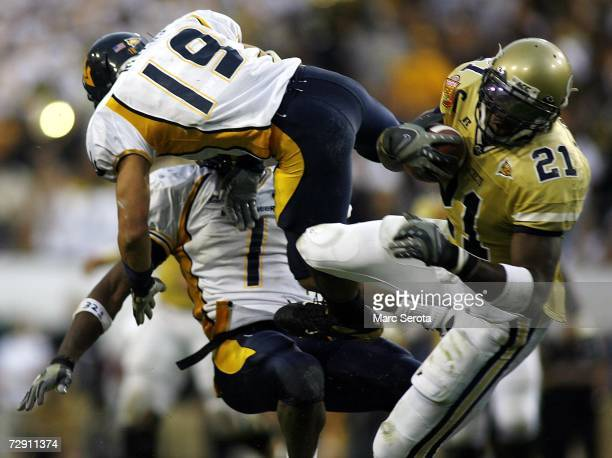 Wide receiver Calvin Johnson of the Georgia Tech Yellow Jackets makes a catch as cornerback Vaughn Rivers and Brandon Myles the West Virginia...
