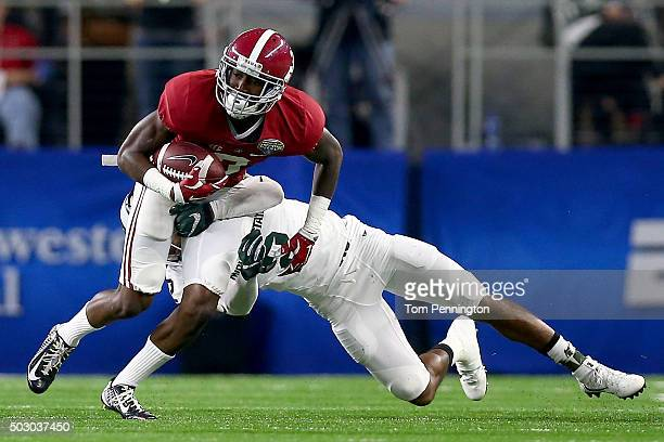 Wide receiver Calvin Ridley of the Alabama Crimson Tide runs after a catch as he is hit by cornerback Darian Hicks of the Michigan State Spartans in...