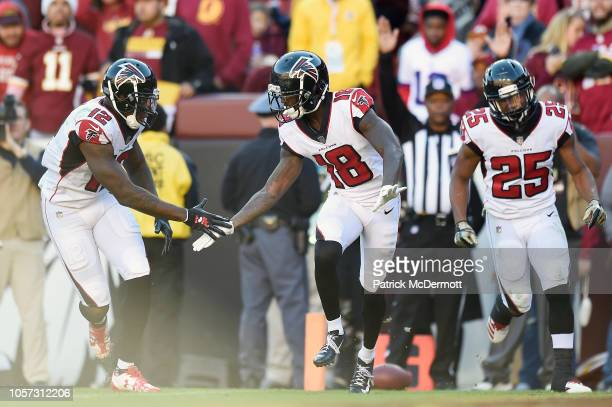 Wide receiver Calvin Ridley of the Atlanta Falcons celebrates with teammates wide receiver Mohamed Sanu and running back Ito Smith after scoring a...