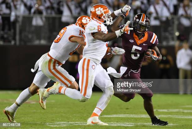Wide receiver Cam Phillips of the Virginia Tech Hokies battles following his reception with linebacker Dorian O'Daniel of the Clemson Tigers in the...
