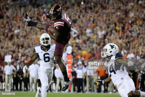 Wide receiver Cam Phillips of the Virginia Tech Hokies catches a pass in front of safety Dravon Askew-Henry and cornerback Hakeem Bailey of the West...