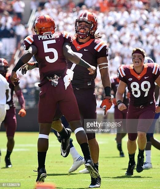 Wide receiver Cam Phillips of the Virginia Tech Hokies celebrates his punt block with tight end Bucky Hodges in the first half against the East...