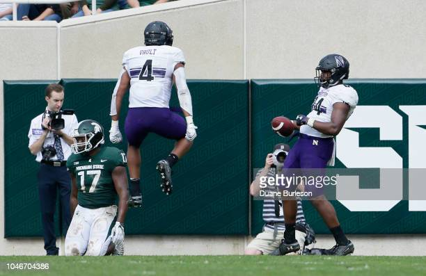 Wide receiver Cameron Green of the Northwestern Wildcats celebrates his touchdown against linebacker Tyriq Thompson of the Michigan State Spartans...