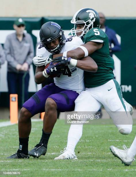 Wide receiver Cameron Green of the Northwestern Wildcats is tackled by linebacker Andrew Dowell of the Michigan State Spartans during the first half...