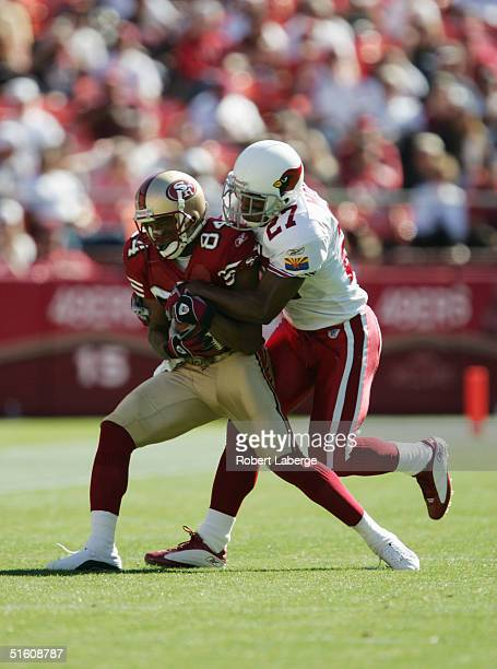 Wide receiver Cedrick Wilson of the San Francisco 49ers tries to break a tackle by cornerback David Macklin of the Arizona Cardinals during the game...