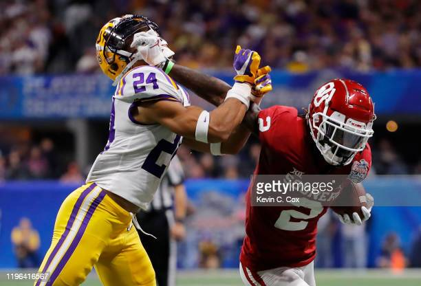 Wide receiver CeeDee Lamb of the Oklahoma Sooners carries the ball against Derek Stingley Jr. #24 of the LSU Tigers during the Chick-fil-A Peach Bowl...